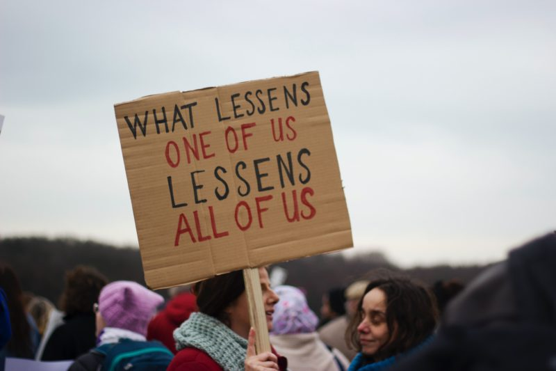 Sign saying what lessens one of us lessens all of us