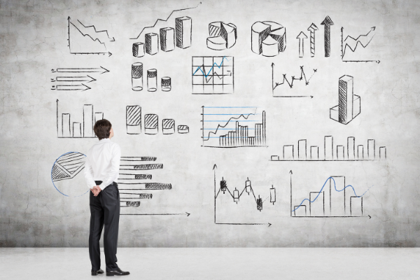 Man standing looking at a wall of graphs